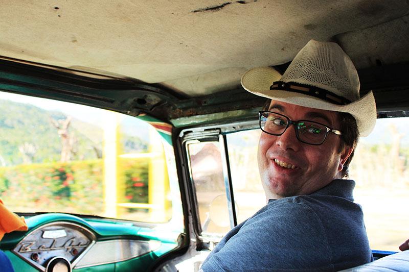 european man traveler white hat smiling inside cuba old taxi