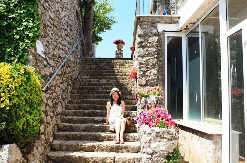 agirlnamedclara female asian traveler white dress hat sits staircase italy capri amalfi coast flower sunshine