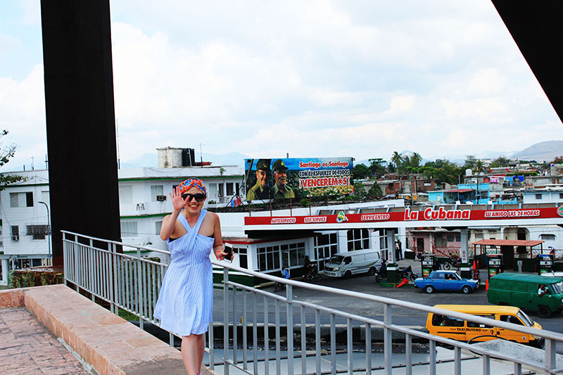 asian girl blue dress orange bandana smiling cuba gas station