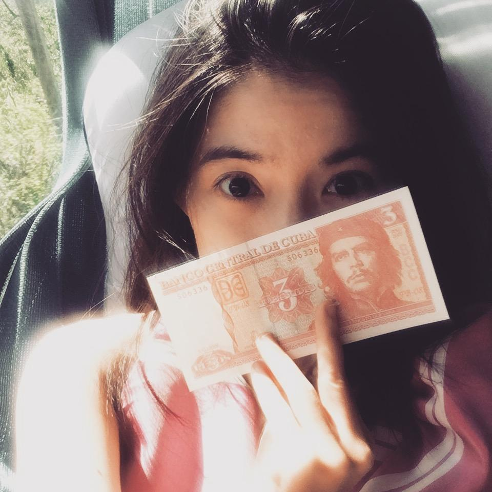 girl holds cuban pesos che gueavara pink clothes