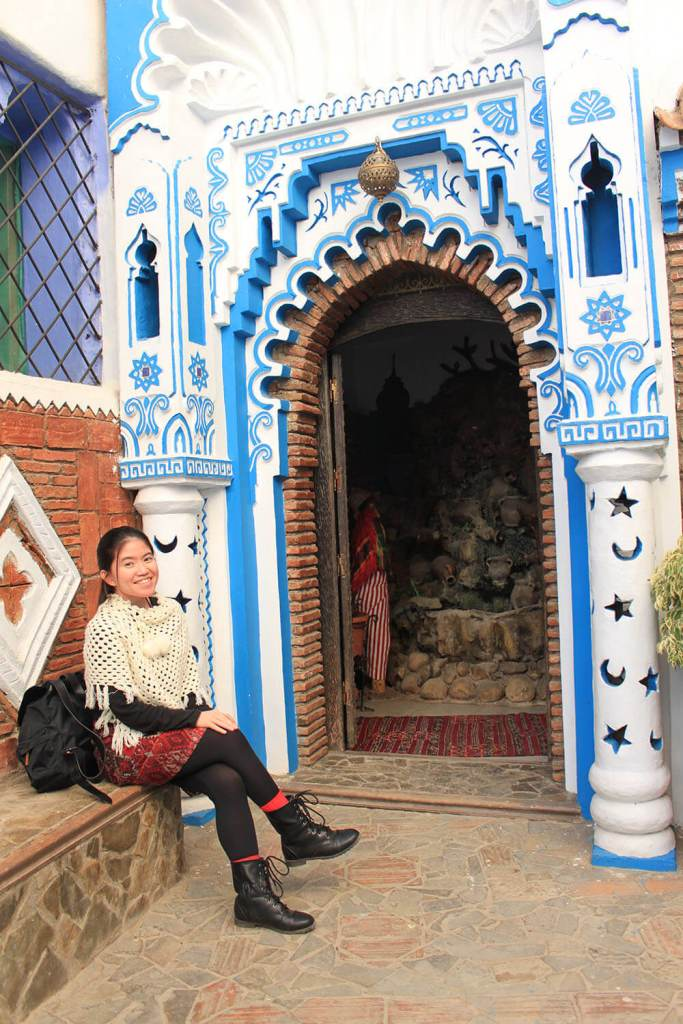 girl sitting white poncho red skirt black boots morocco blue city chefchaouen door islamic design_agirlnamedclara