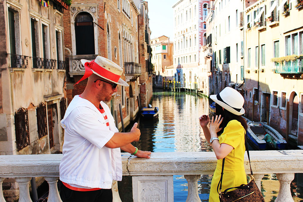 agirlnamedclara female traveler yellow dress gondola italian man venice bridge