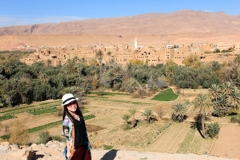 asian girl solo female traveler smile white fedora black top valley of thousand kasbahs morocco background sunny day blue sky