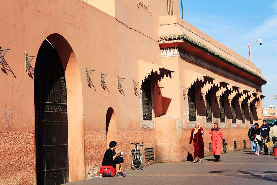 Marrakech souk Morocco female traveler sits on her luggage against a wall blue sky agirlnamedclara