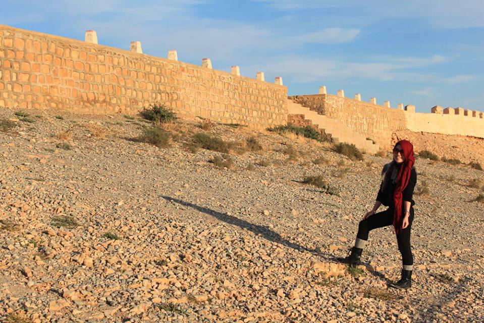 girl red scarf black boots standing morocco rocks castle border background blue skyagirlnamedclara
