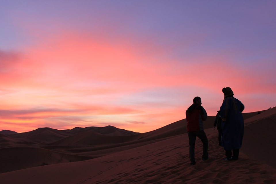 two men standing with sunrise purple red sky background sahara desert morocco agirlnamedclara
