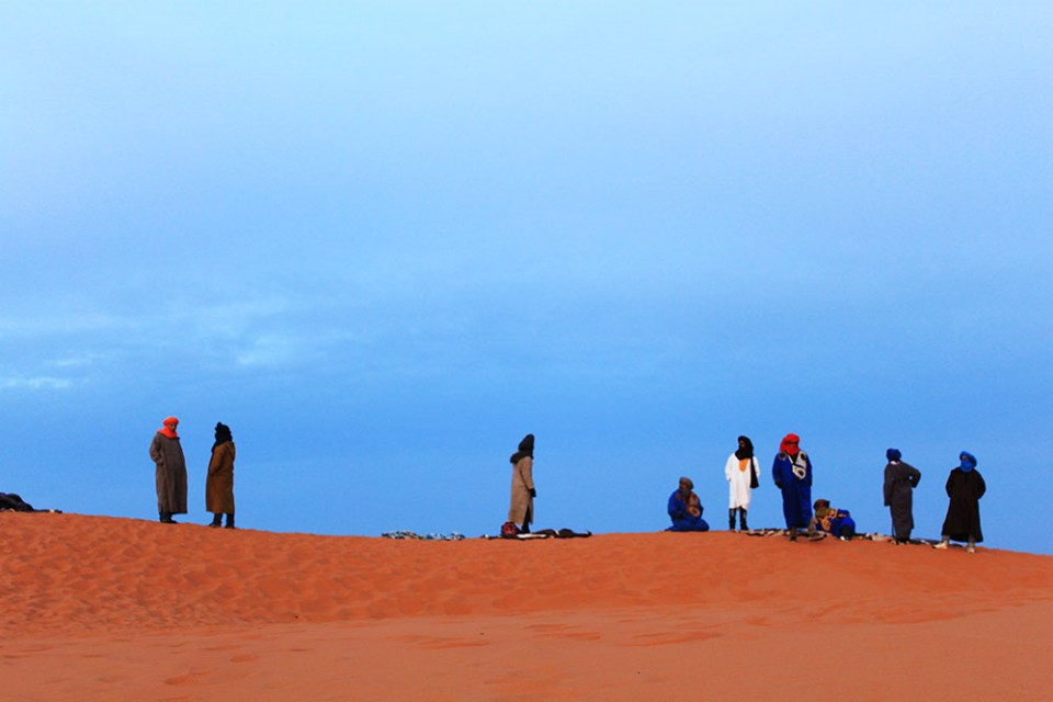 clear blue morning sky men in traditional clothes sahara desert morocco agirlnamedclara