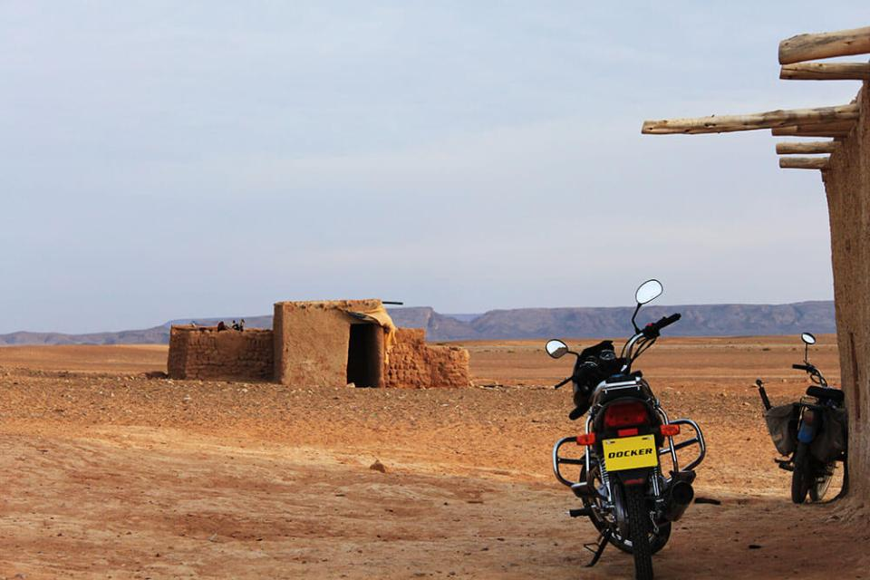motorbike in the middle of rocky desert sahara morocco berber village agirlnamedclara