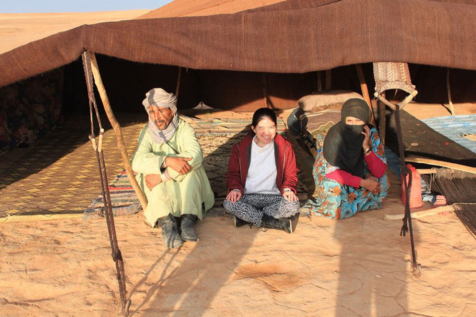 asian girl sitting in the middle of local nomads tent sahara desert morocco agirlnamedclara