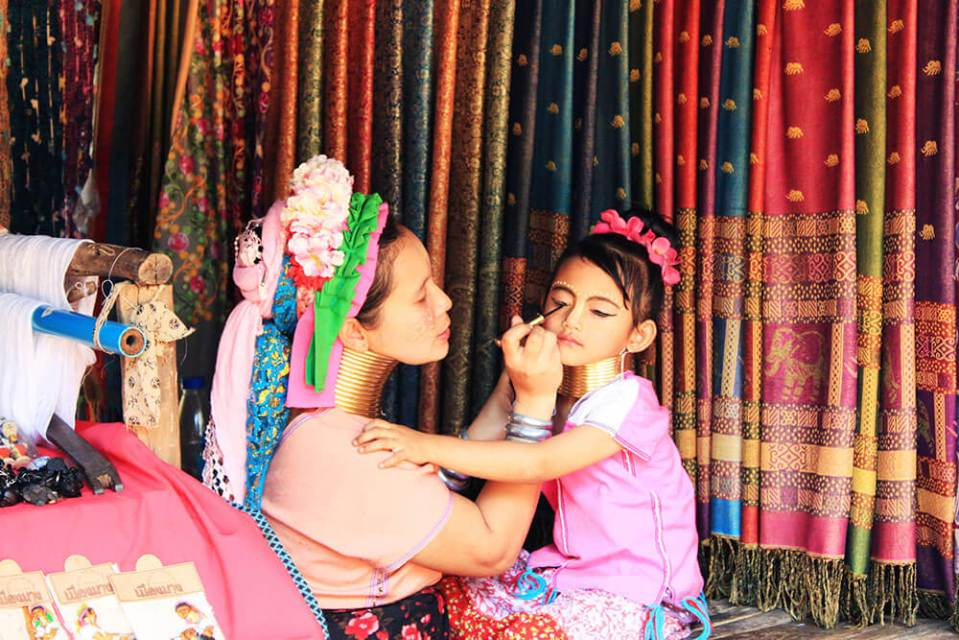 long neck woman drawing eyeliner makeup on her long neck little daughter textile background long neck tribe village chiang mai agirlnamedclara