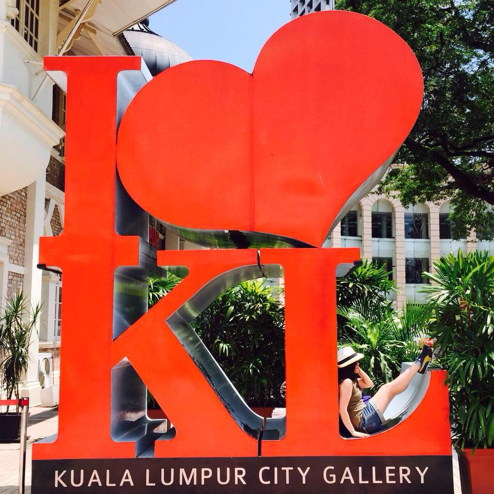 agirlnamedclara kuala lumpur one day travel itinerary girl sitting on i love kl red signboad