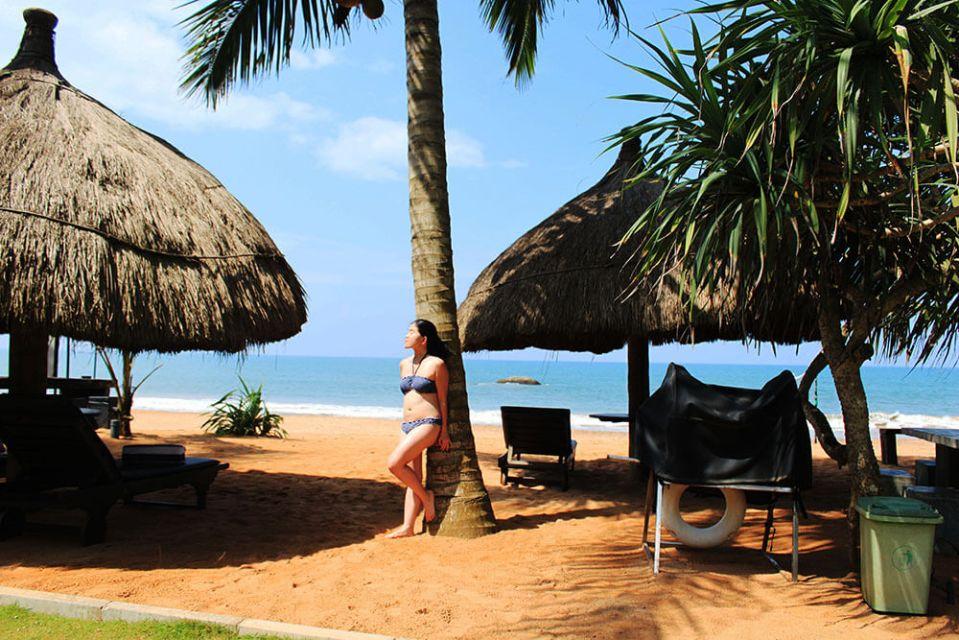 asian girl in hairbun blue bikini leaning on coconut tree white sand beach bentota sea rock villa sri lanka agirlnamedclara