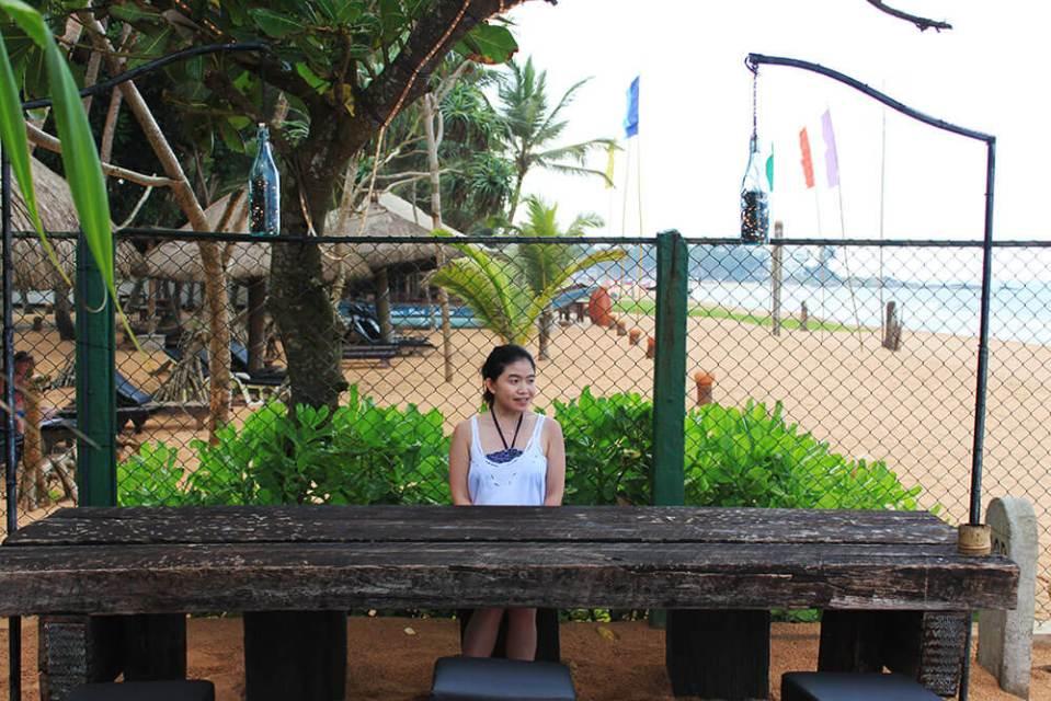 asian girl smiling sitting wood bench table private beach bentota sea rock villa sri lanka agirlnamedclara