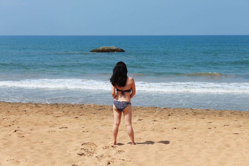 small petite asian girl facing back blue sea with black hair in blue bikini standing on bentota beach sri lanka blue sky agirlnamedclara
