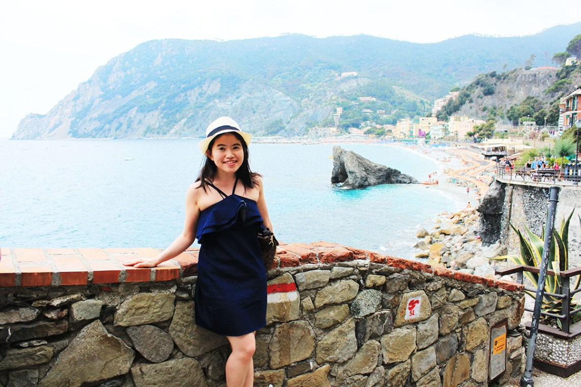 asian girl solo traveler smiling blue denim jeans dress white straw hat sea background cinque terre italy agirlnamedclara