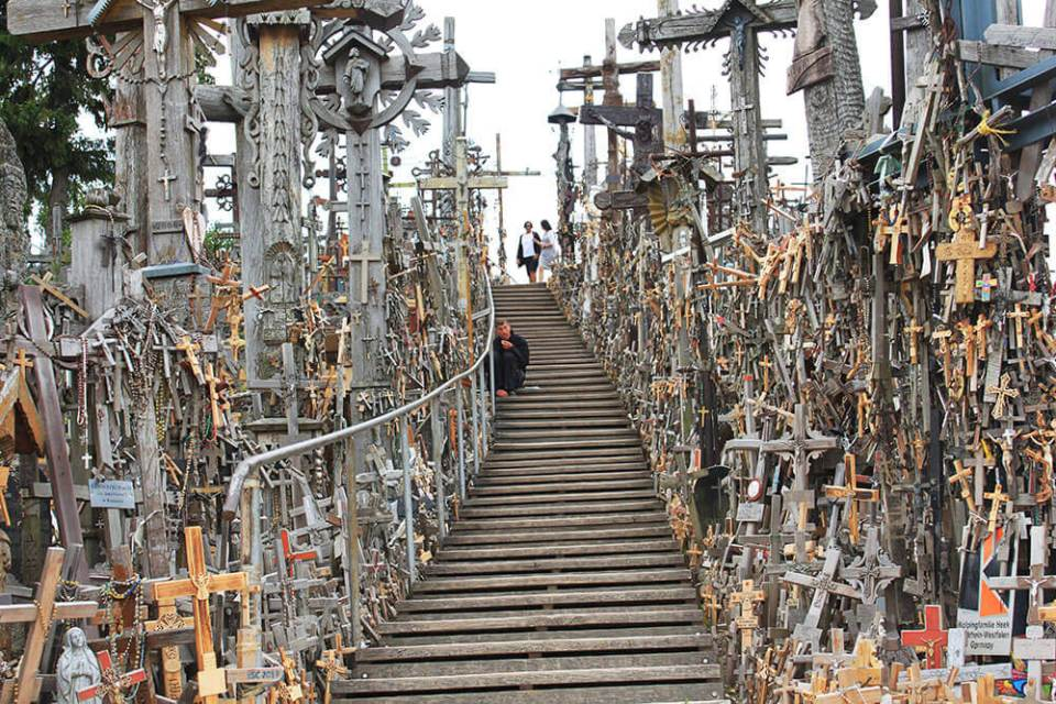 a beggar sitting on staircases surrounded by crosses Hill of Cross Lithuania Happy Easter_agirlnamedclara
