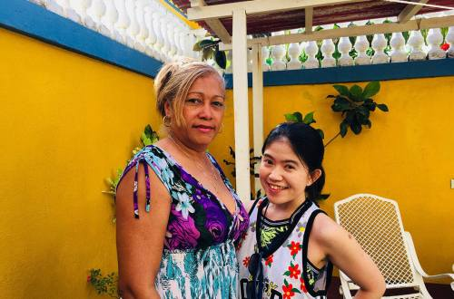 asian girl tourist traveler with cuban woman host smiling casa homestay yellow wall background_agirlnamedclara