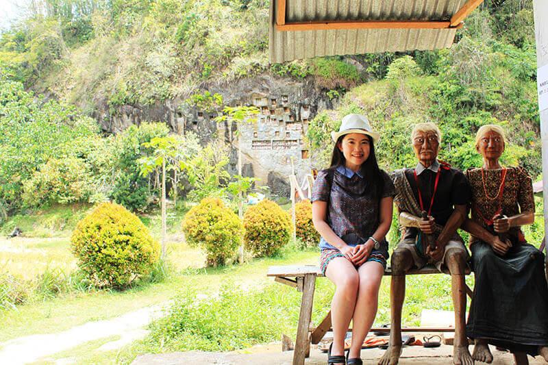 asian girl long hair smile sit beside tau tau wooden dolls toraja londa background_agirlnamedclara