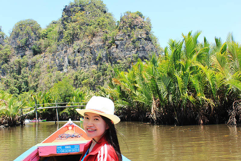 asian girl white rattan hat smiling on a boat palm oil tree bukit rammang rammang makassar toraja indonesia_agirlnamedclara