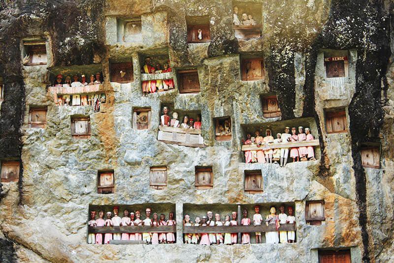 close up shot of tau tau wooden dolls in sqare burial holes londa toraja trip sulawesi indonesia_agirlnamedclara