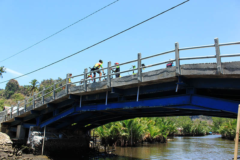 cyclist group on a bridge bukit rammang rammang makassar indonesia_agirlnamedclara