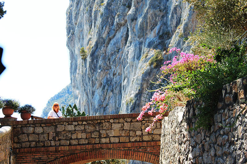 woman stand alone on stone  bridge flower capri italy summer agirlnamedclara