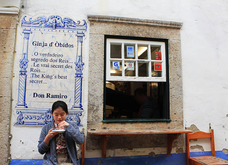 asian girl sit in front of ginja shop drink obidos agirlnamedclara