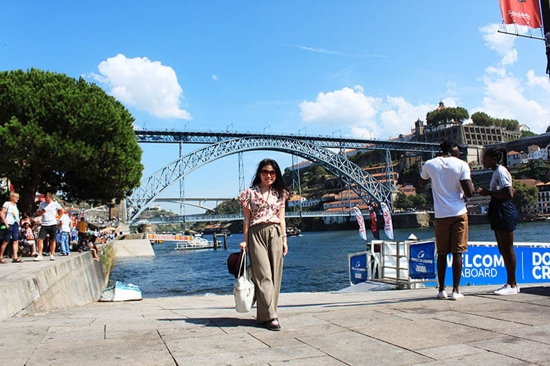 asian girl smile zara outfit in front of porto bridge summer blue sky sea agirlnamedclara