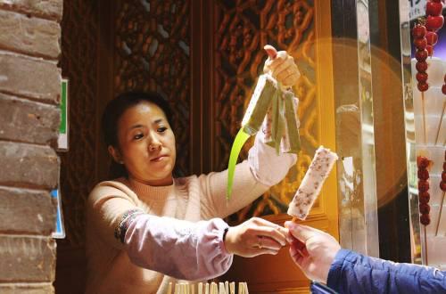 woman sell glutinous rice stick rectangle sweet street snack in houhai beijing agirlnamedclara