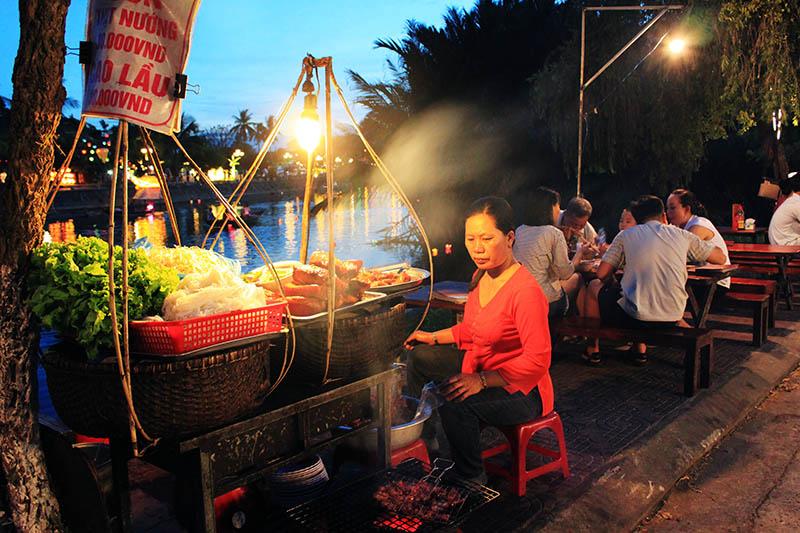 woman night market stall sit by river hoi an agirlnamedclara
