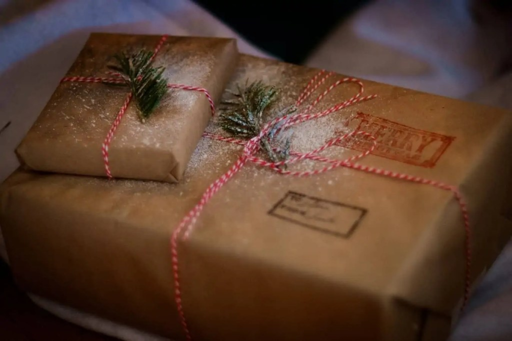 Two Christmas gifts wrapped in brown paper