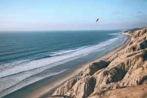 ridge against foamy sea under flying paragliders