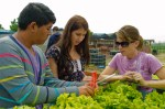 Students Saul Ramos and Paige Coffman with their instructor Audrey Bonomi measuring the growth of their lettuce.
