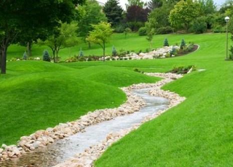 stream of water flowing through grassy hills