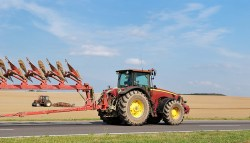 Tractor moving plough on the road