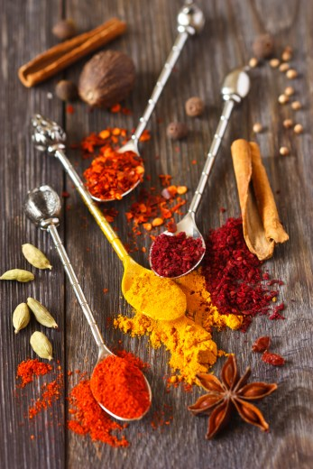 Assortment of spices and herbs on an old wooden background.
