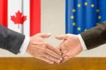 Representatives of Canada and the EU shake hands trade deal