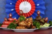 Super Bowl Sunday football party celebration food plates with chicken buffalo wings, meat balls, hot dogs and USA party decorations.