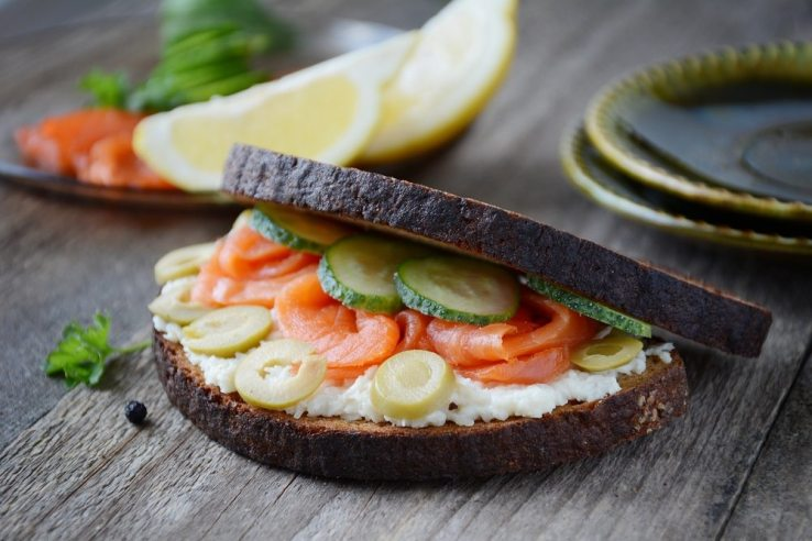 Smoked salmon sandwich with green olives, cucumber, horseradish cheese spread n rye bread.