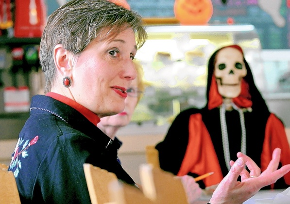 "Gail Rubin hosts a Death Café at Sheila's Sweets, wearing the skull-decorated shirt she likes to put on for death-related events and interviews. Seated alongside her is a pearl necklace-wearing skeleton she named Lola, because ""whatever Lola wants, Lola gets — death is sort of like that,"" Rubin says. (Jim Thompson/Albuquerque Journal)"