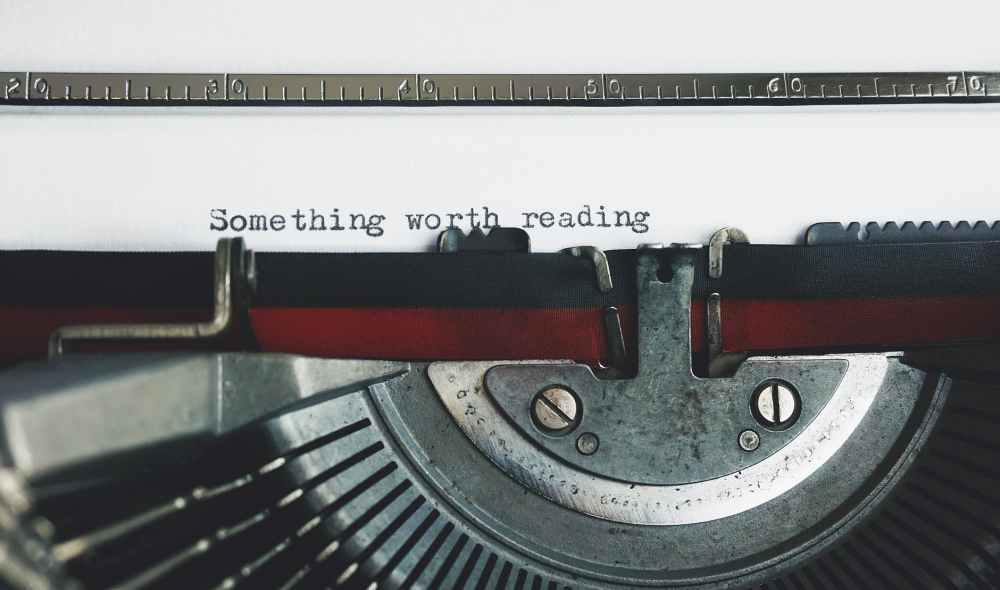 black and red typewriter on white table