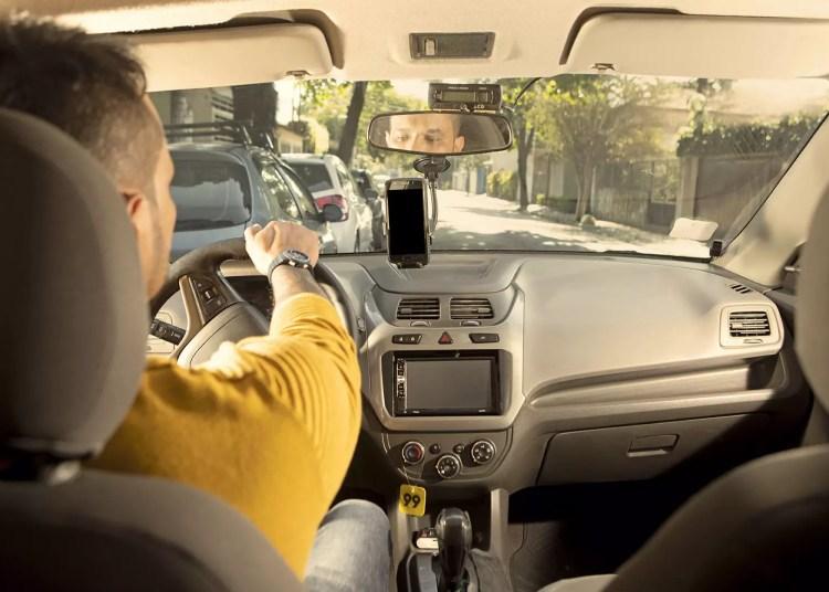 Acampamento Farroupilha de 99. Um homem de blusão amarelo dirige um automóvel.