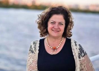 Porto Alegre Convention: Uma mulher sorri ao posar com um rio atrás.