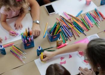 TRIS. Pelo menos três crianças pintam com diversos lápis e canetas coloridas.