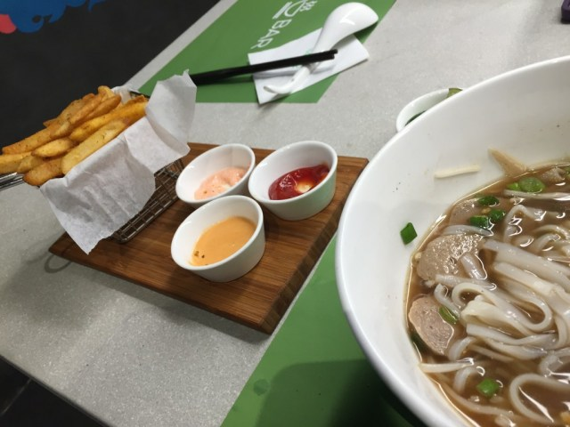 Pho and curry fries with three dipping sauces from a small establishment hidden behind a clothing stall in a narrow alley