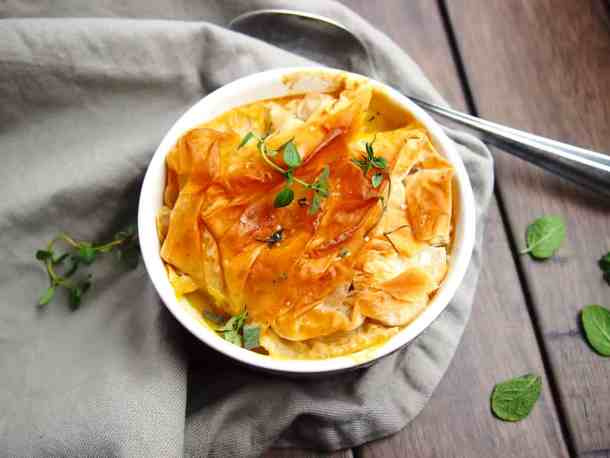 Overhead view of pot pie with herbs scattered.
