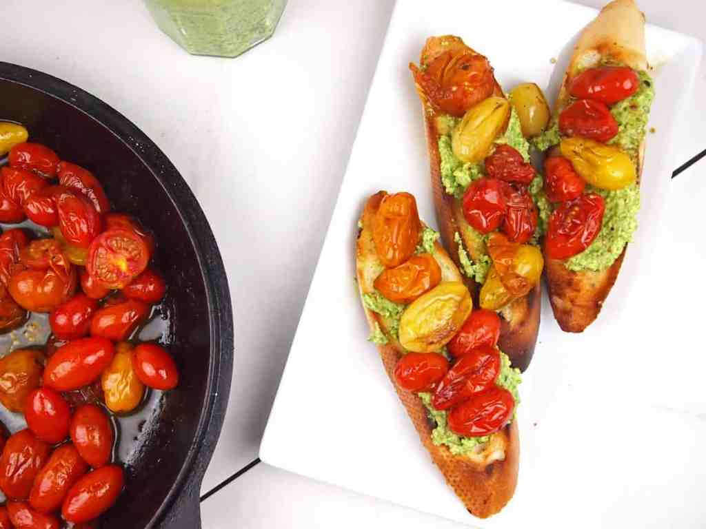 Roasted tomatoes in a cast iron skillet with bruschetta on the side.