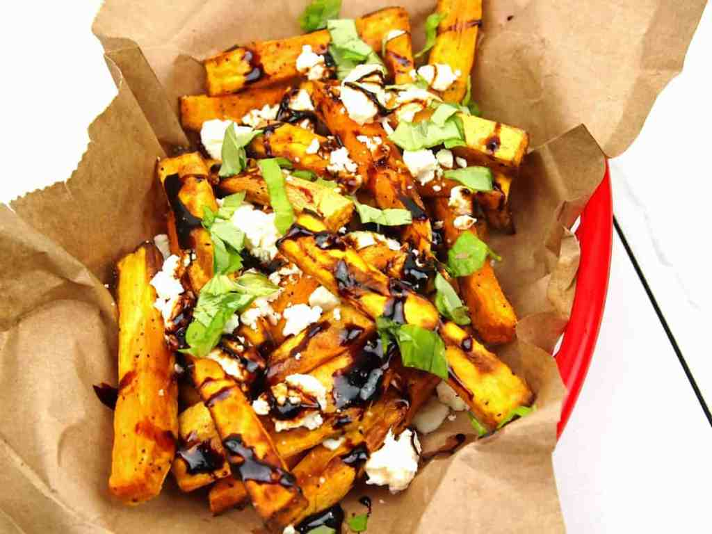 close-up of loaded Greek fries with feta, basil, and balsamic glaze