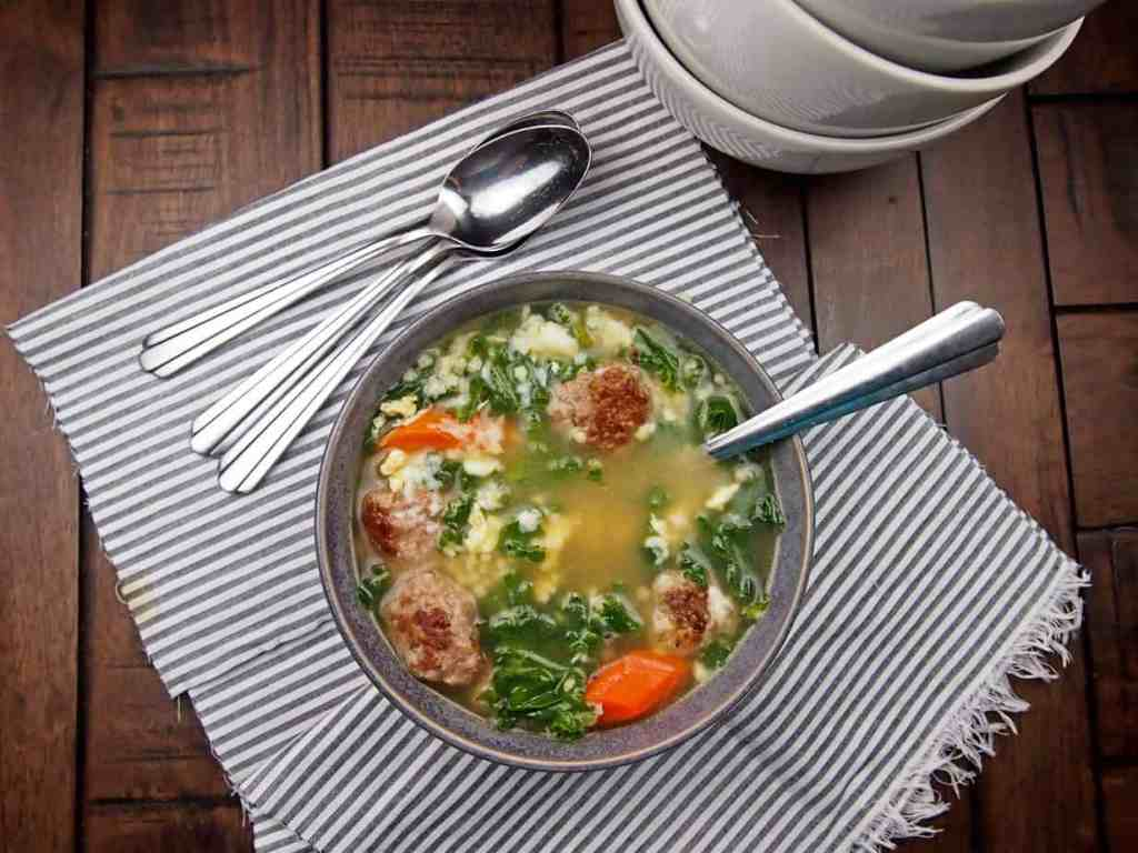Italian wedding soup with meatballs, carrots, onions, and kale