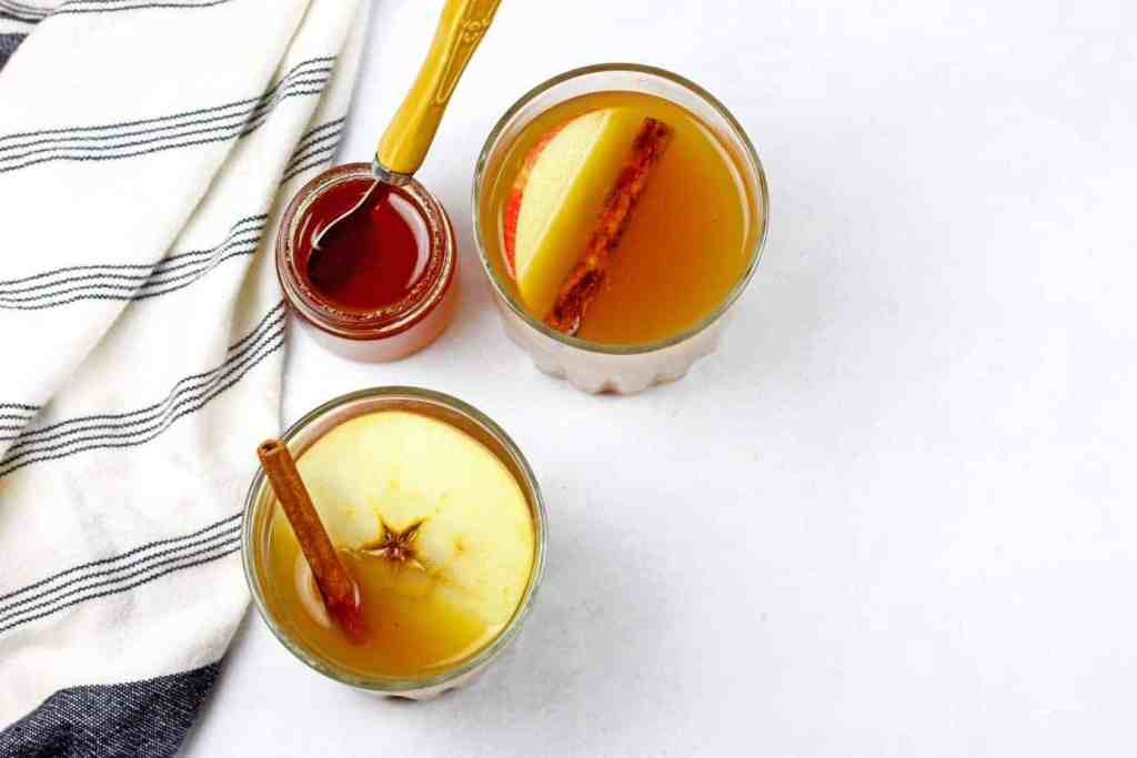 Overview of two apple cider hot toddy with a pot of honey with a spoon and towel on the side on a white countertop.